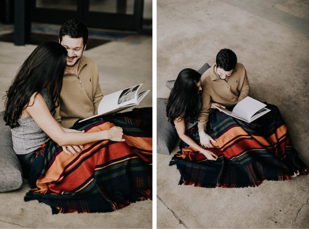 engaged couple reading and snuggling up with each other during their at-home engagement photos