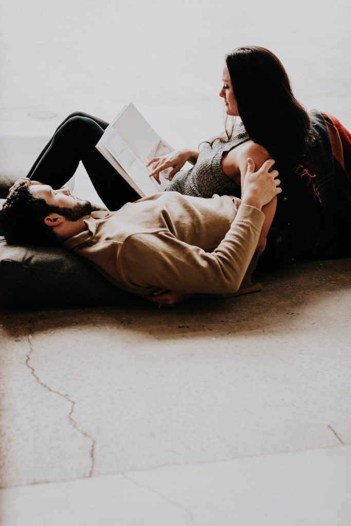 engaged couple reading to each other and snuggling up with each other during their at-home engagement photos