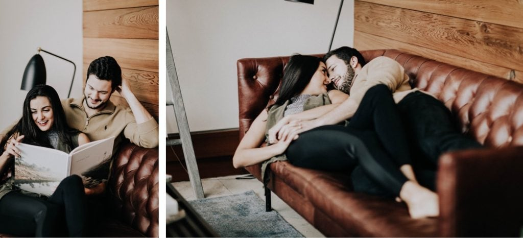 couple sitting on the couch and reading to each other during their at-home engagement photos
