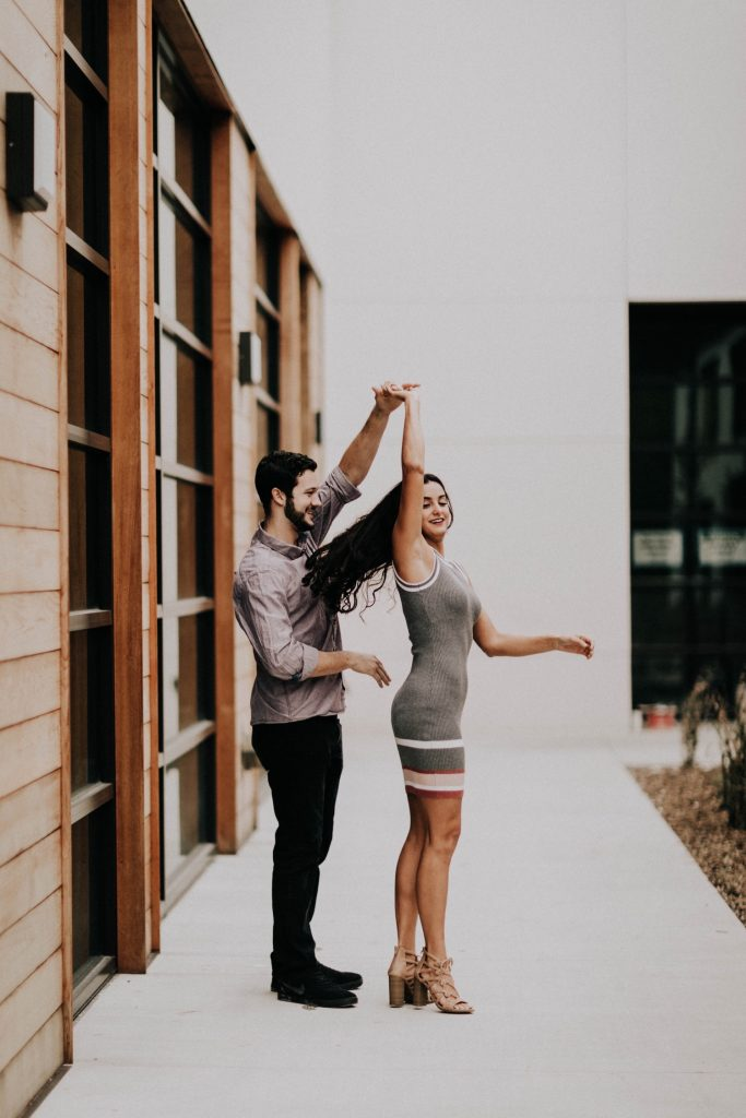 couple dancing together outside apartment during t heir at-home engagement