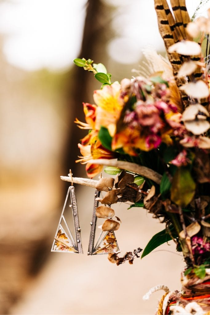handmade boho earrings hanging off a bouquet for a Colorado van life wedding elopement