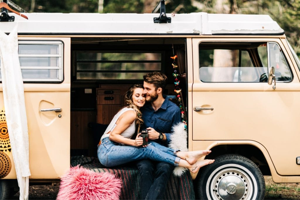 couple drinking coffee together in their camper van before their Rocky Mountain camper van wedding elopement