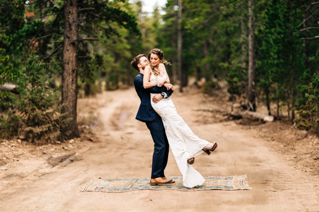 couple twirling around on a dirt road during their camper van elopement wedding in the Colorado Rocky Mountains
