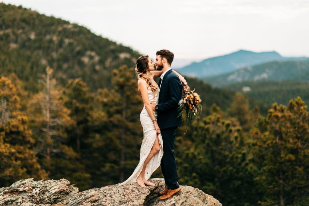 couple kissing on a mountain cliff in the Rocky Mountains during their camper van elopement wedding