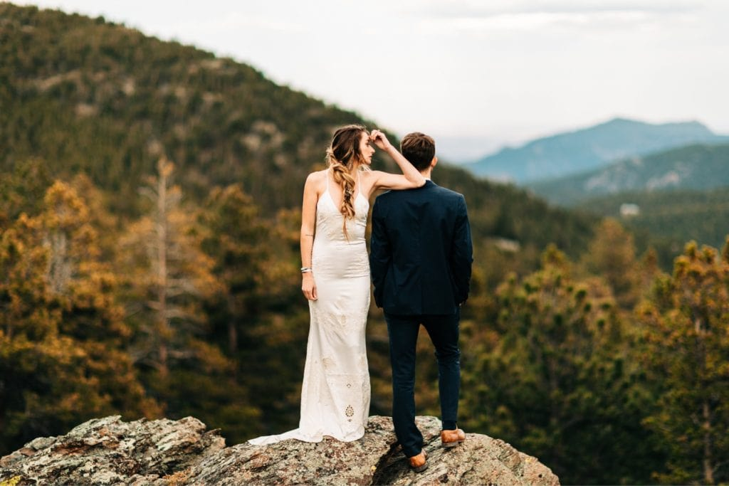 couple standing on a mountain cliff in the Rocky Mountains during their camper van elopement wedding