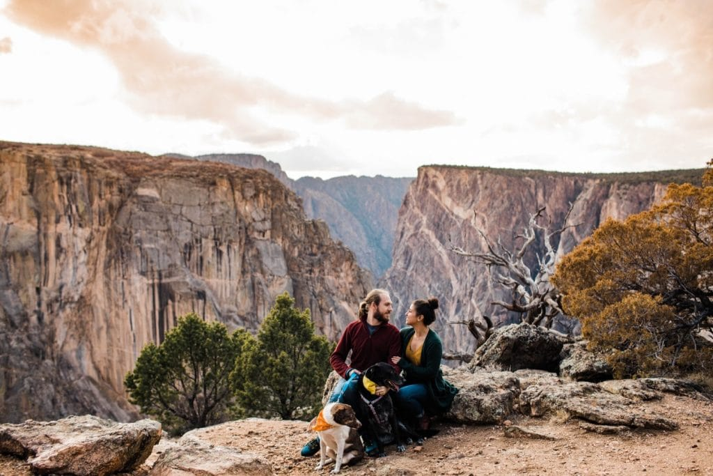 couple sitting on the edge of a canyon cliff with their two dogs