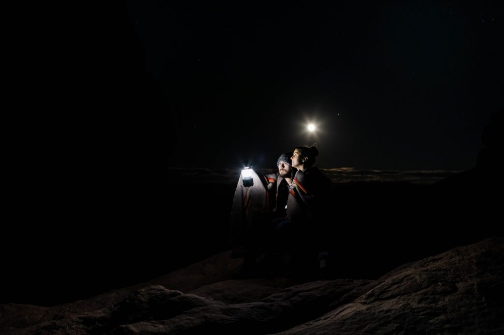 night time adventurous engagement photos of a couple in Moab Utah with a full moon