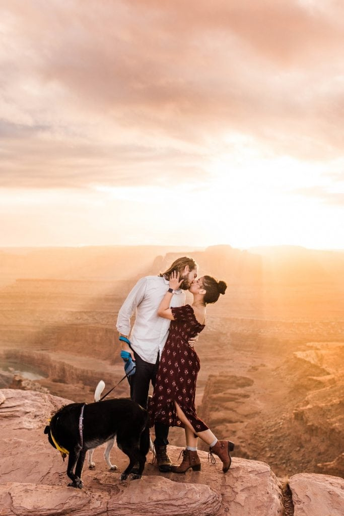 engaged couple kissing on the edge of a cliff at sunset in Moab Utah