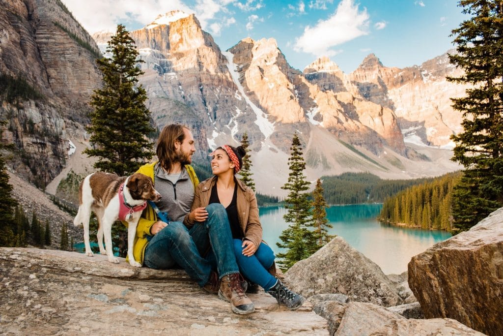 couple sitting in the mountains with their dog