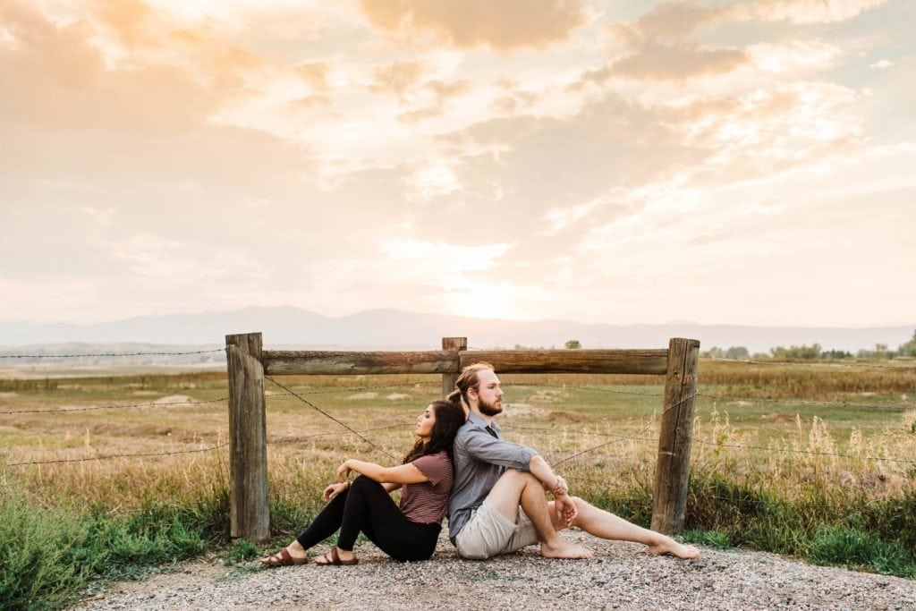 couple sitting back to back in front of the Rocky Mountains in Longmont