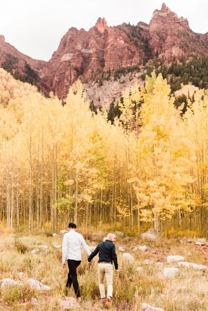 groom and groom walking through the mountains of Aspen Colorado during their Maroon Bells proposal