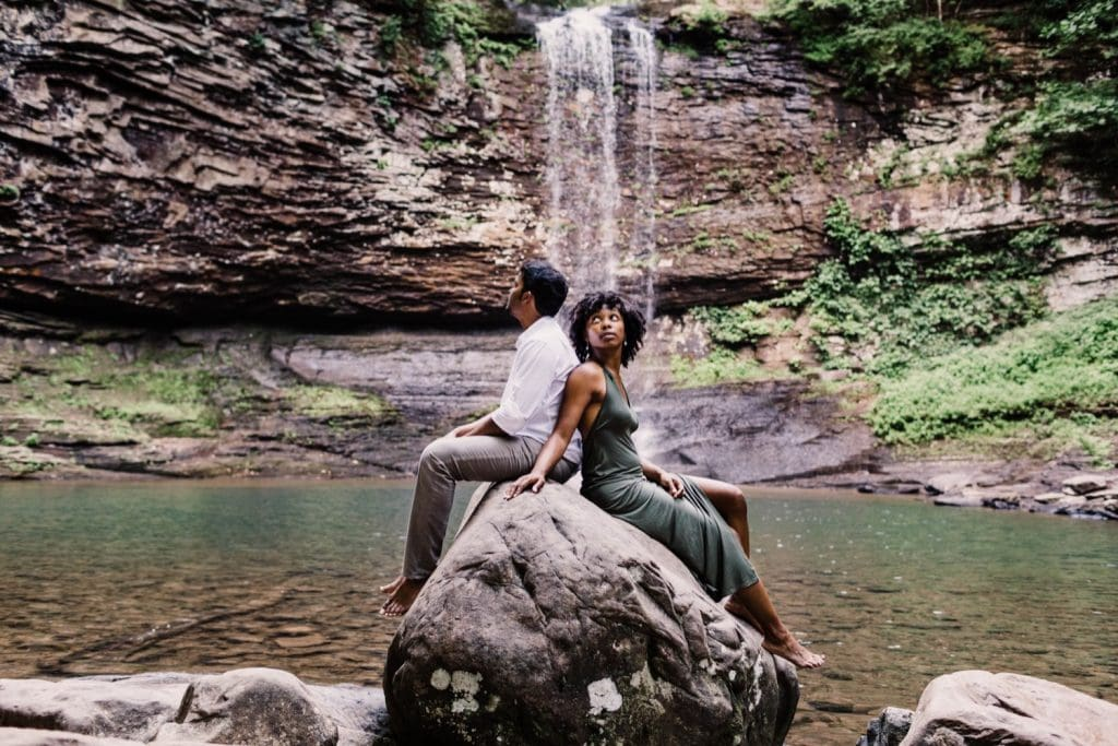 engaged couple sitting on a giant rock during their waterfall engagement photos