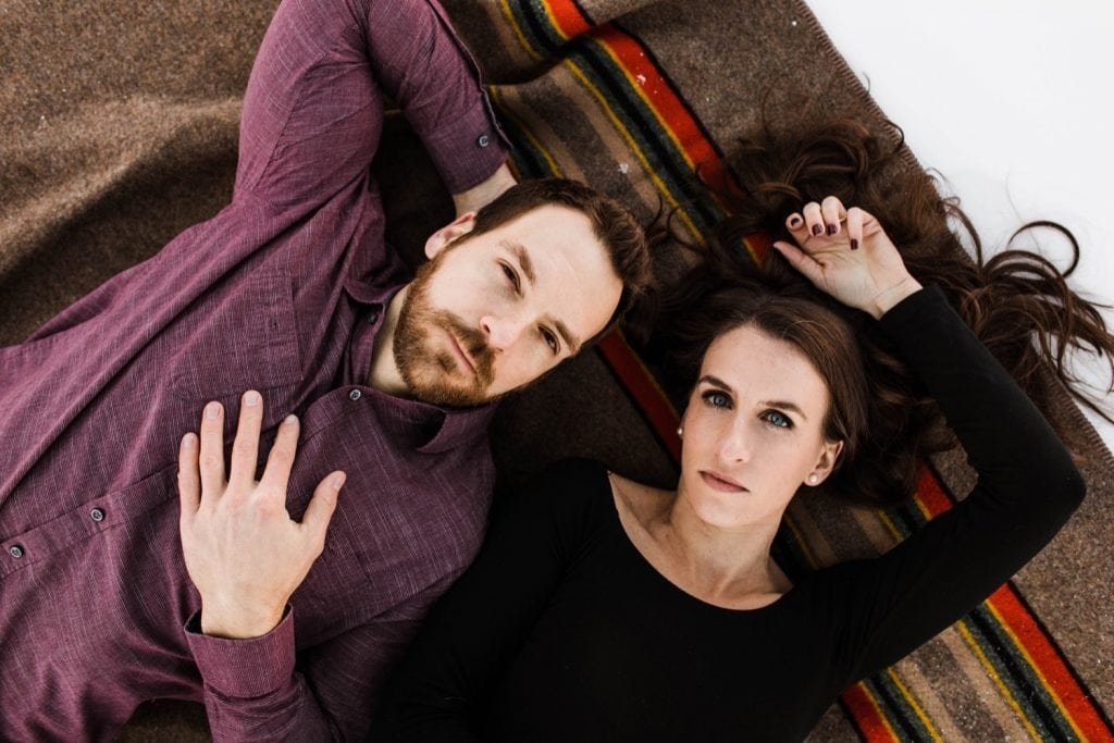 couple laying on a Pendleton Yakima blanket during their snowy Colorado engagement session