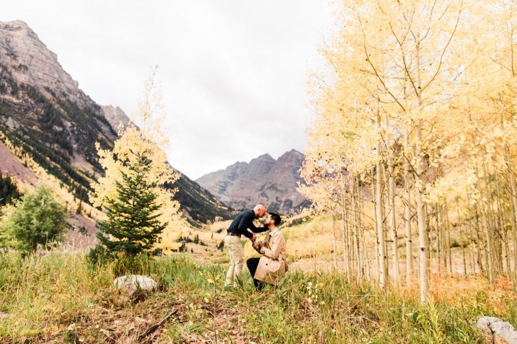 groom gets down on one knee to propose to his boyfriend at Maroon Bells in Aspen Colorado