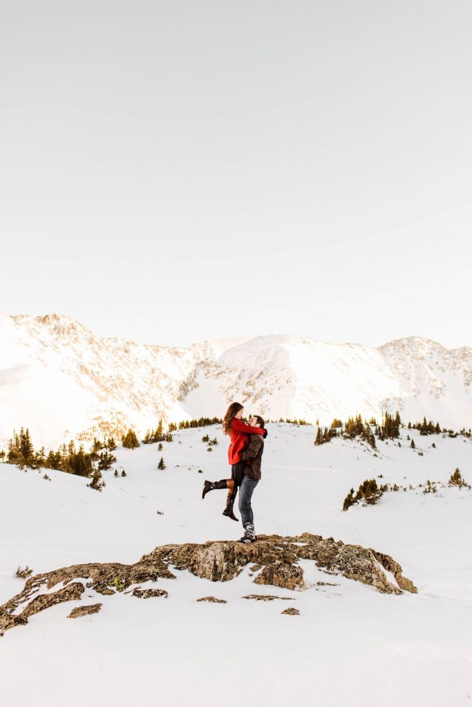 couple hiking a mountain during their snowy Colorado engagement photos in the Rocky Mountains of Colorado