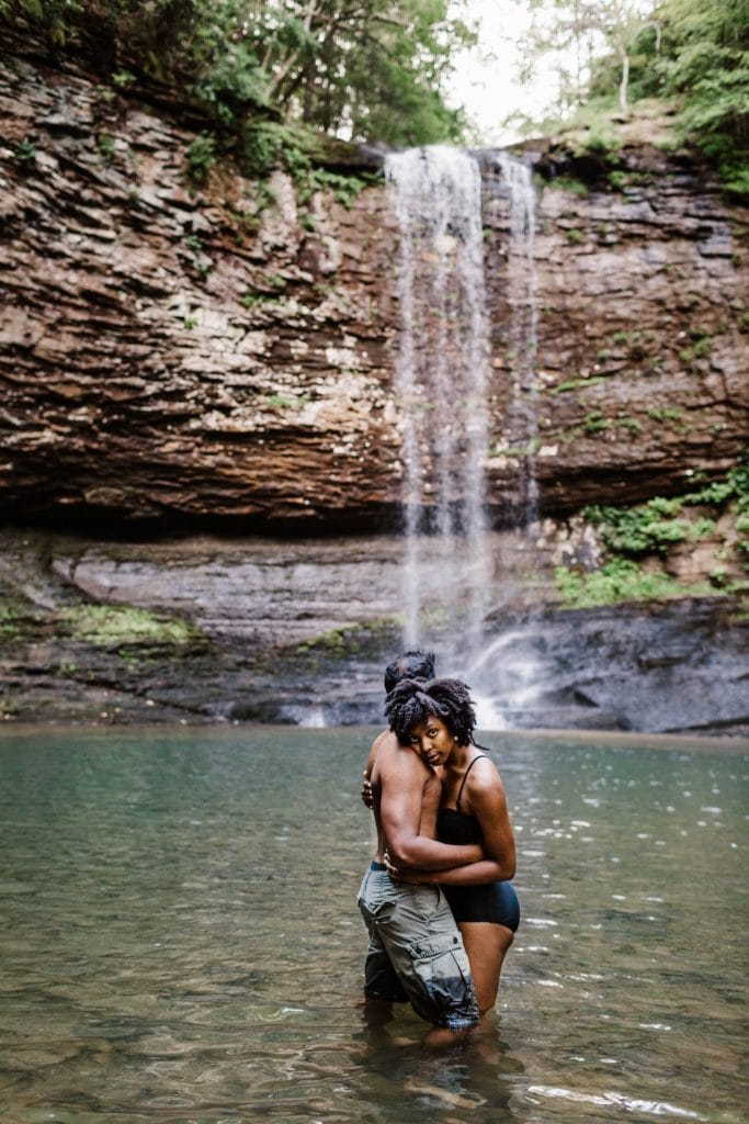 engaged couple playing in waterfall during their waterfall engagement photos