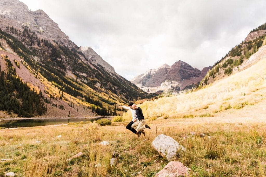newly engaged same sex couple jumping off a rock in the mountains of Aspen Colorado after their Maroon Bells proposal