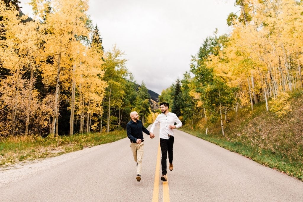 newly engaged same sex couple running through the mountains in Aspen Colorado after their Maroon Bells proposal