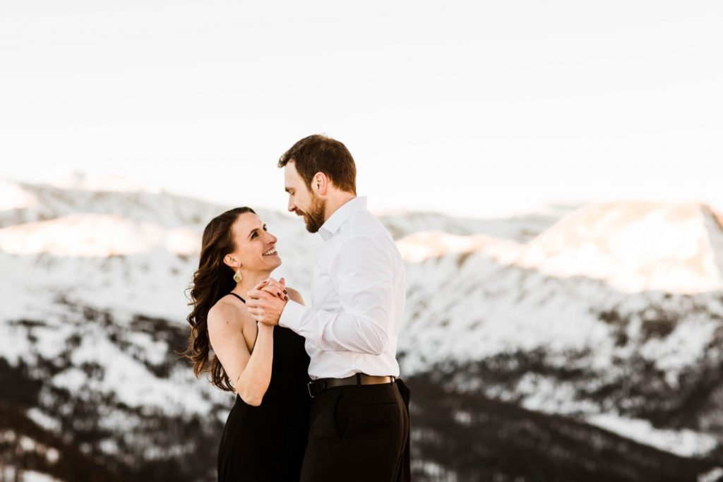 couple dancing in the snowy Rocky Mountains during their snowy Colorado engagement photos