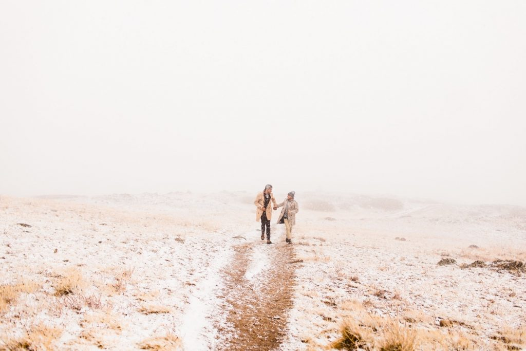 same sex couple running through the snow during their Maroon Bells Aspen Colorado proposal