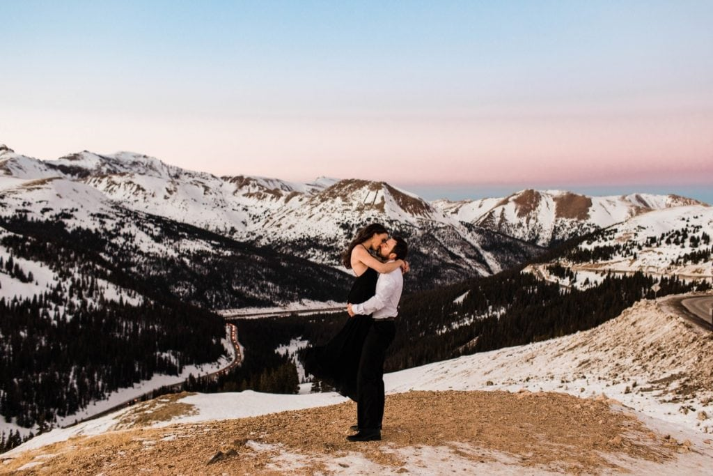 groom lifting bride during their snowy Rocky Mountain Colorado winter engagement photos