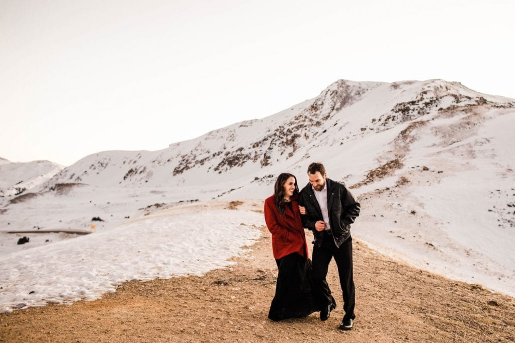 engaged couple laughing and running through the snowy mountains during their Colorado winter engagement photos in the Rockies