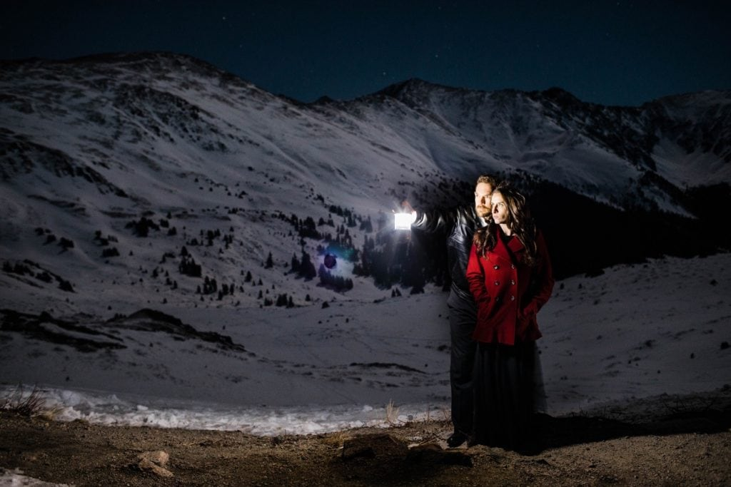snowy engagement photos of a couple standing underneath a wintry sky full of stars in the Rocky Mountains of Colorado