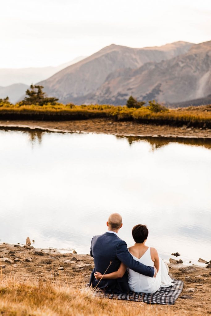 couple snuggling by a mountain lake during their Rocky Mountain post-wedding adventure session in Estes Park