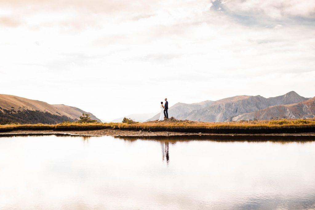 couple walking around a mountain lake during their Rocky Mountain post-wedding adventure session in Estes Park