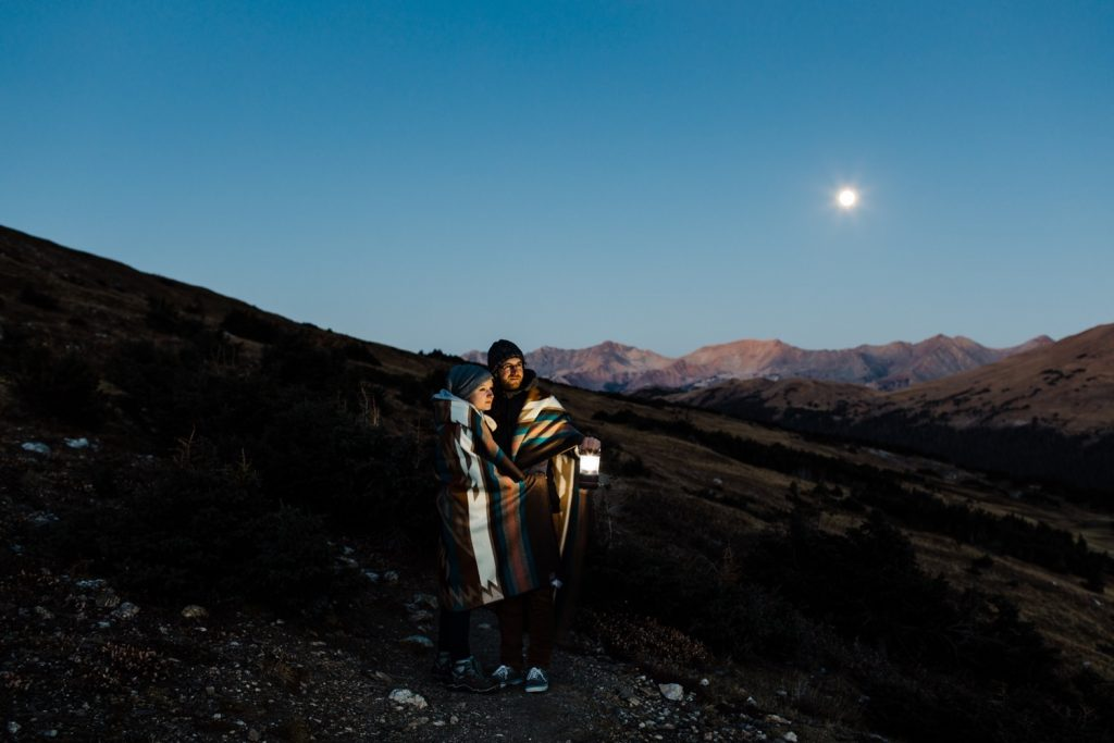 engaged couple hiking at night during their sunrise Rocky Mountain National Park engagement session in Colorado | Rocky Mountain elopement photographers