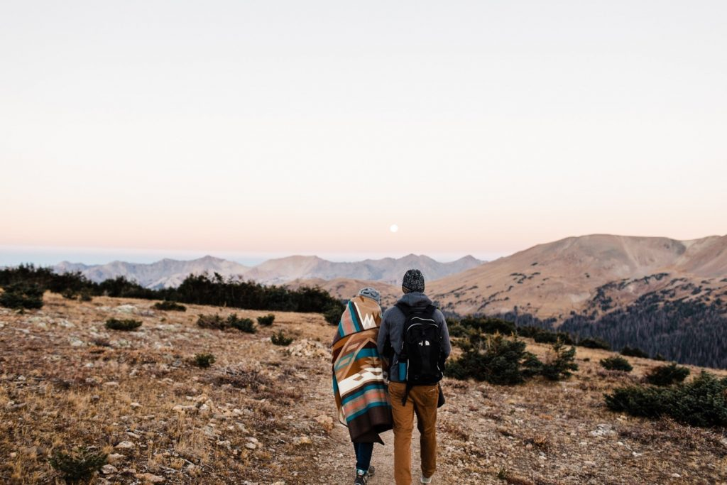 couple hiking at sunrise in the Colorado mountains for their Rocky Mountain National Park engagement session