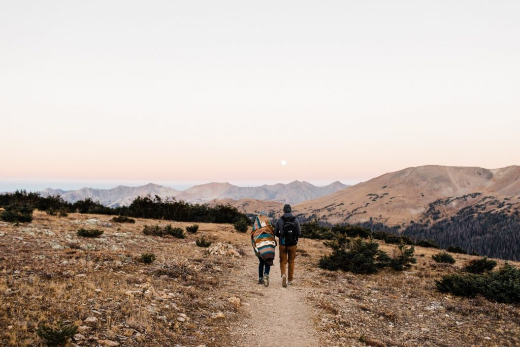 couple hiking at sunrise in the Colorado mountains for their Rocky Mountain National Park engagement photos