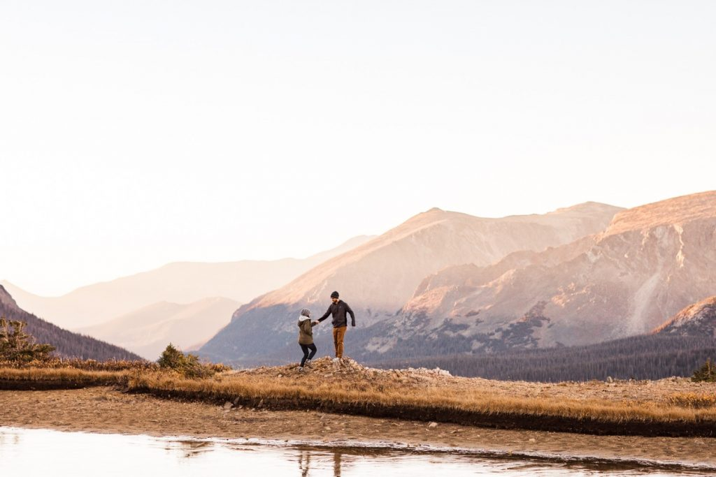 couple hiking around an alpine lake in the Rocky Mountains during their engagement session | Rocky Mountain elopement photographers