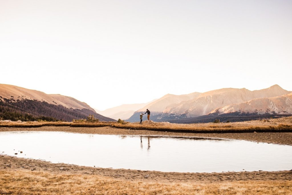 couple hiking around an alpine lake in the Rocky Mountains during their engagement session