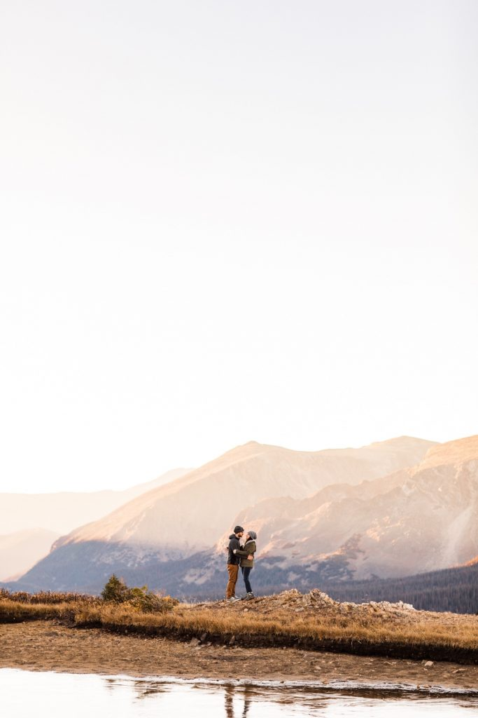 adventurous engaged couple hiking around an alpine lake in the Rocky Mountains during their engagement session