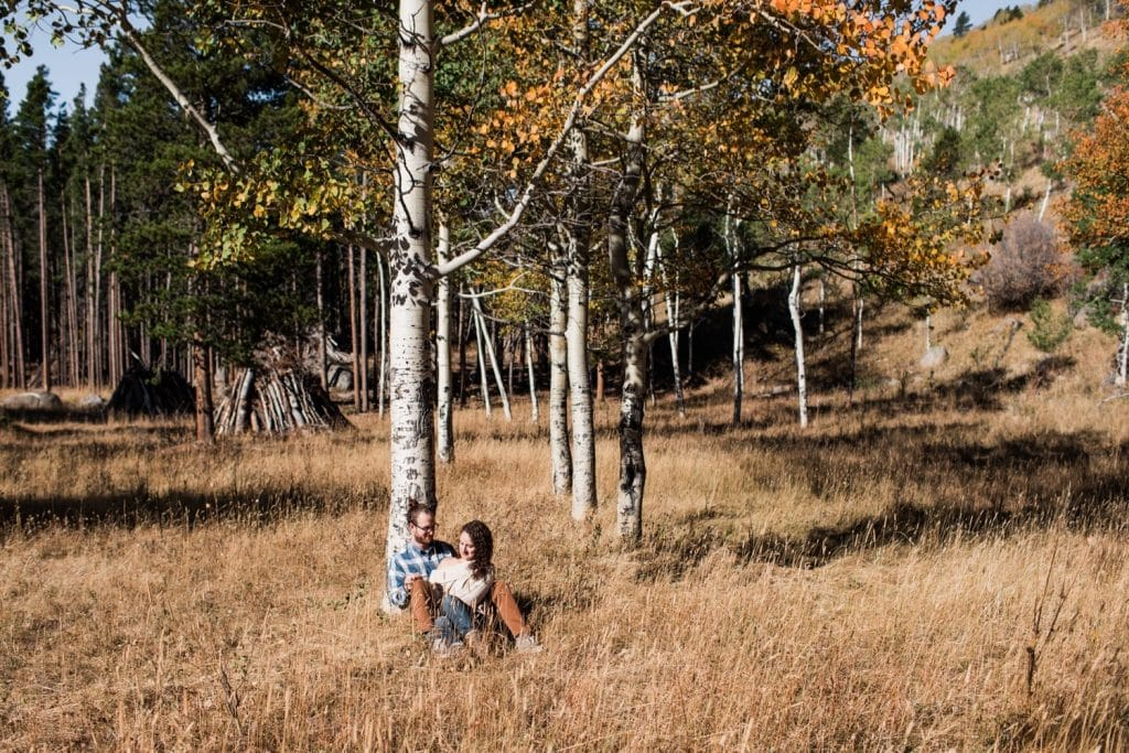 engaged couple sitting beneath aspen trees during their Rocky Mountain National Park engagement session in September