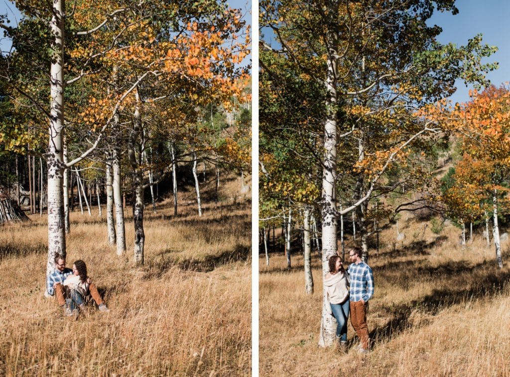 engaged couple sitting beneath aspen trees during their Rocky Mountain National Park engagement session in September | Rocky Mountain elopement photographers