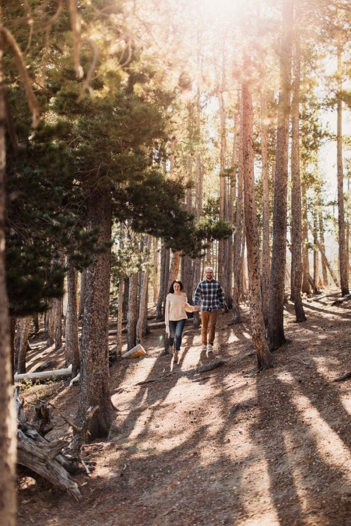 adventurous engaged couple running through the woods at sunrise during their Rocky Mountain National Park engagement photos in Colorado | Rocky Mountain elopement photographers