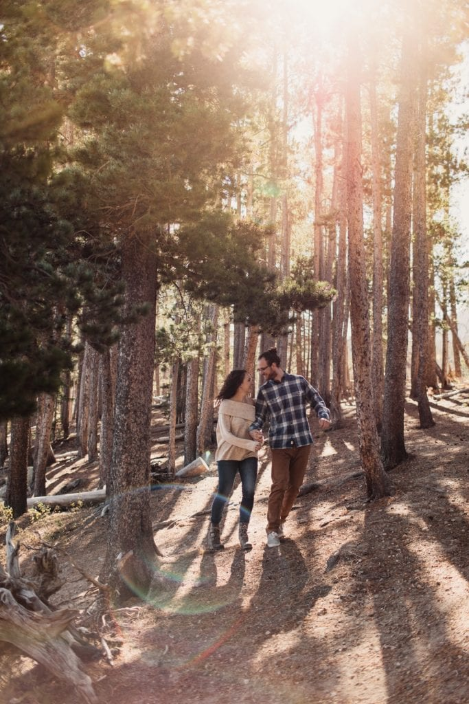 adventurous engaged couple running through the woods at sunrise during their Rocky Mountain National Park engagement photos in Colorado
