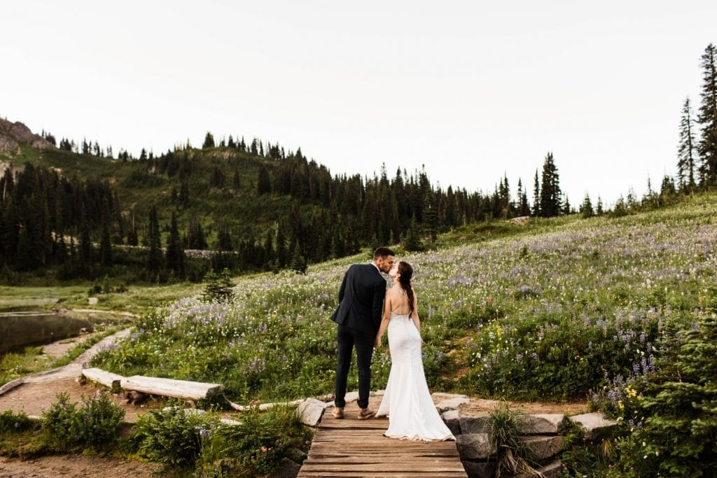 couple walking on a mountain bride together during their adventurous national park elopement in Mt Rainier | Washington state elopement and adventure wedding photographers