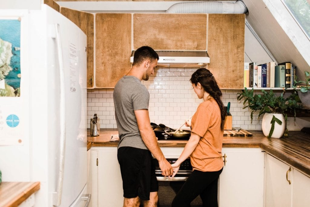 couple cooking breakfast in an a-frame cabin after their Mount Rainier elopement | Washington state elopement adventure wedding in the mountains