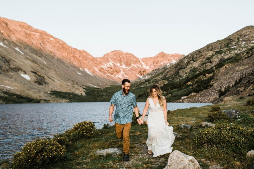 engaged couple running together in the mountains during their Breckenridge adventure engagement photos at an alpine lake | Breckenridge elopement and wedding photographers