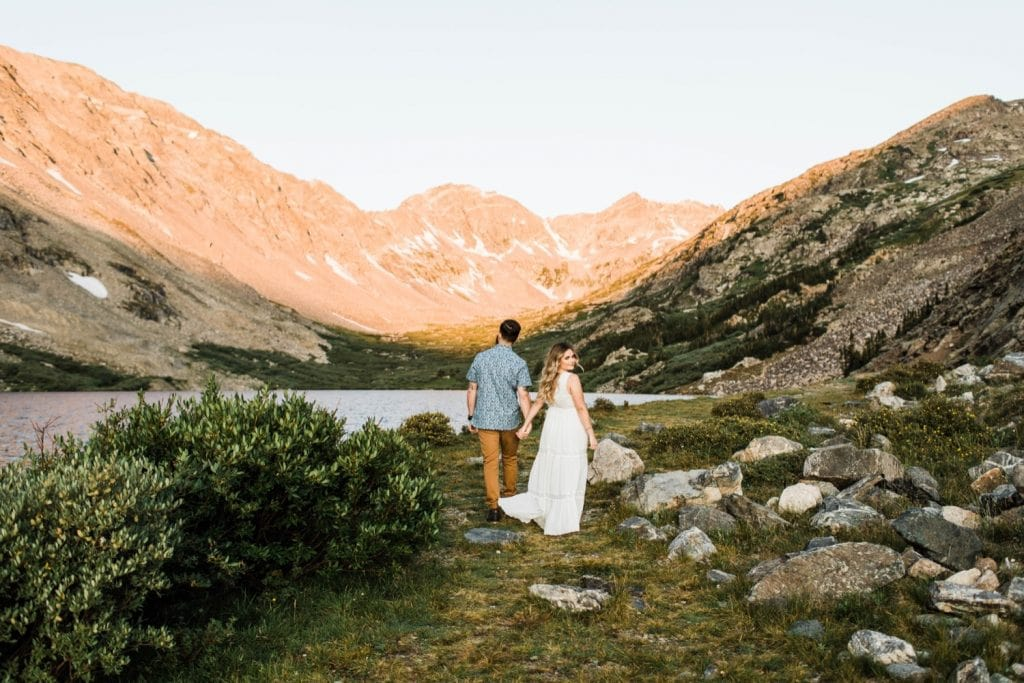 eloping couple walking through the mountains during their adventurous engagement photos in Breckenridge | Colorado elopement and mountain wedding photographers