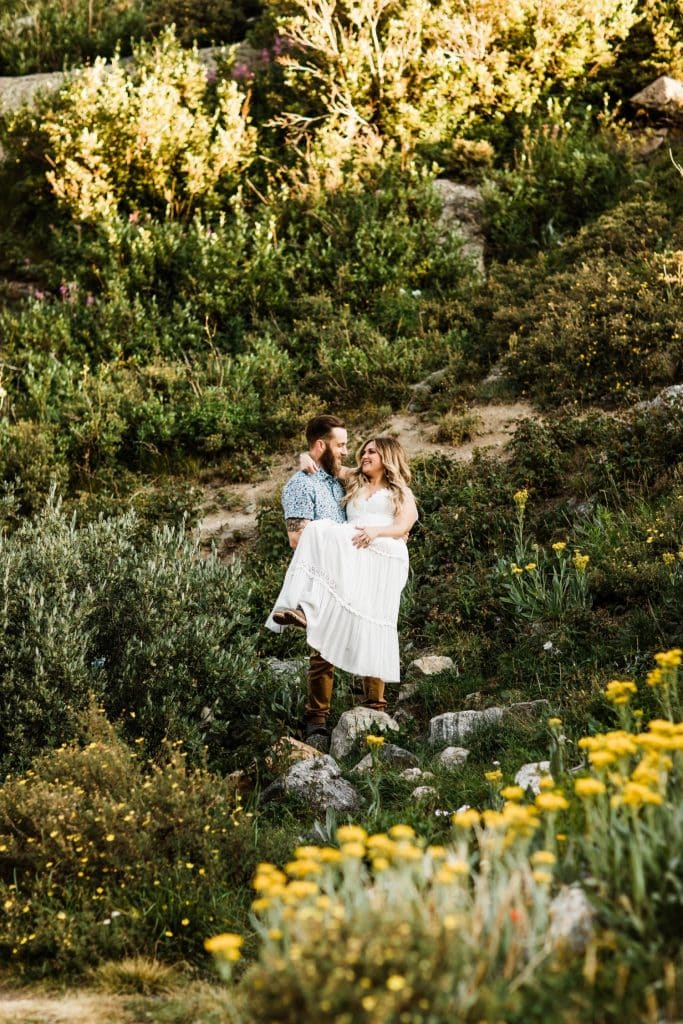 groom holding bride in a mountain wildflower meadow during elopement style photos in Colorado | Breckenridge wedding and elopement photographers