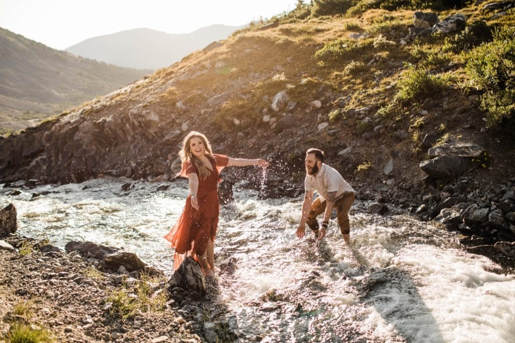 eloping couple splashing each other in a creek during their adventurous engagement photos in the mountains of Colorado | Breckenridge wedding photographers