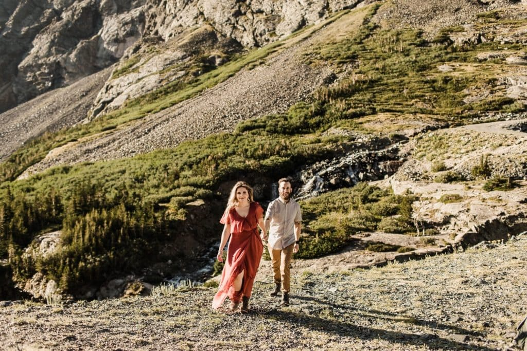 eloping couple walking through the Rocky Mountains of Colorado at sunrise | best wedding photographers in Breckenridge