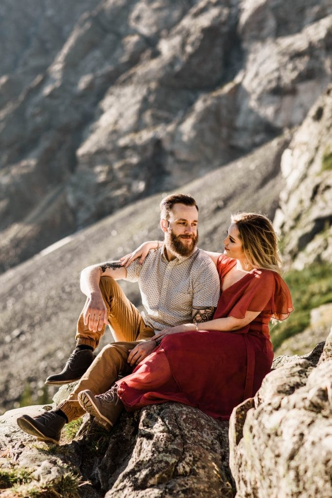 eloping couple sitting at an overlook near an alpine lake in Colorado while getting their engagement photos taken near Breckenridge Colorado