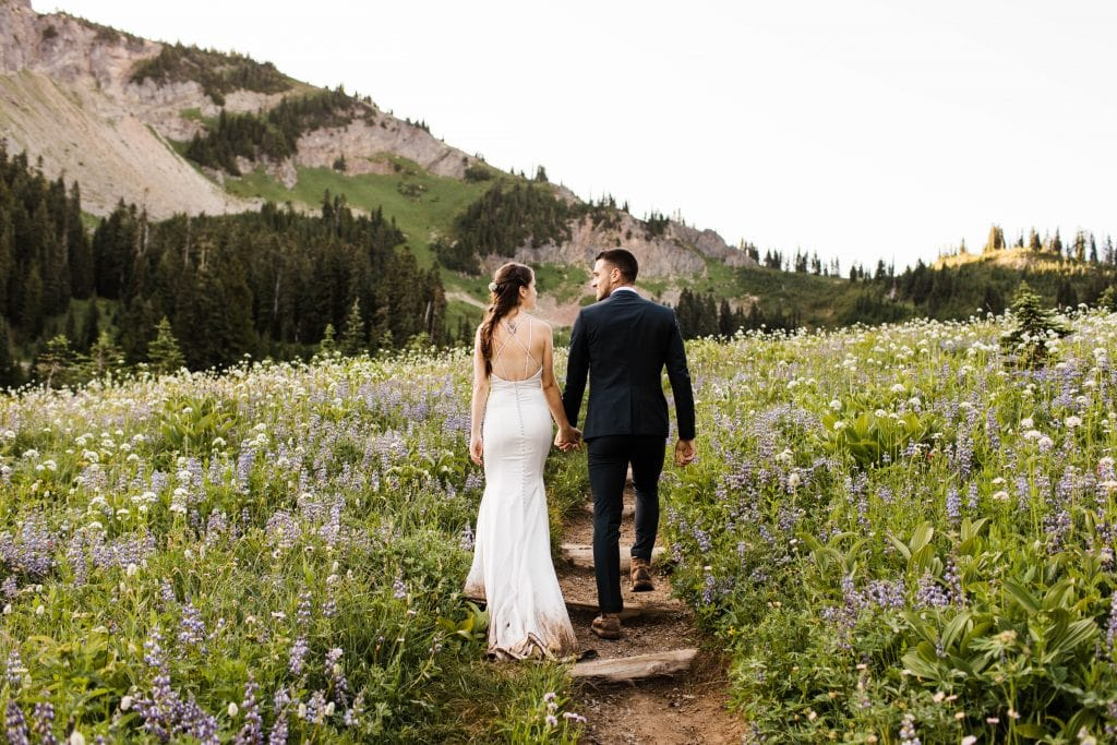 Eloping couple hiking through mountains during their adventure wedding in Mt Rainier Washington state | taken by Colorado elopement photographers