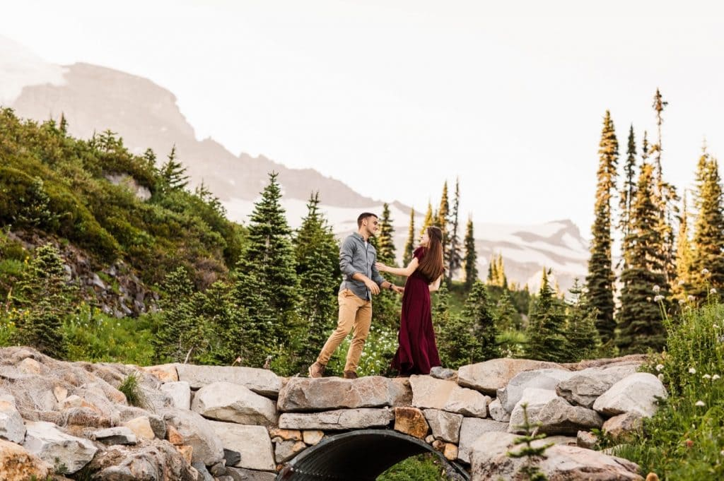 engaged couple running through the mountains during their engagement photos in Seattle WA