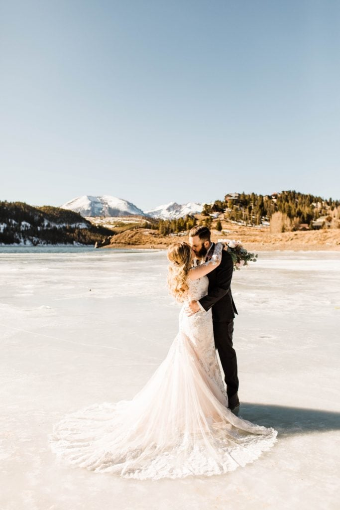 couple kissing on the ice of Dillon Reservoir before their Sapphire Point Overlook wedding ceremony